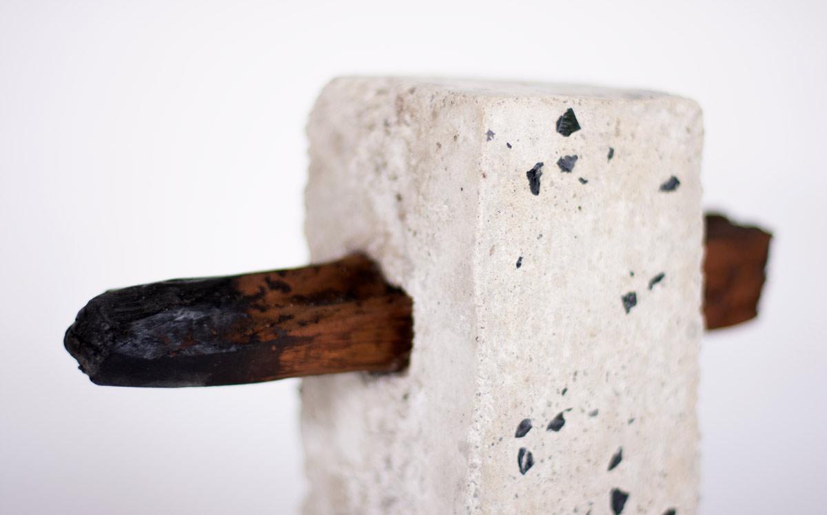 Sculpture. Concrete block with burnt red gum pierced through centre
