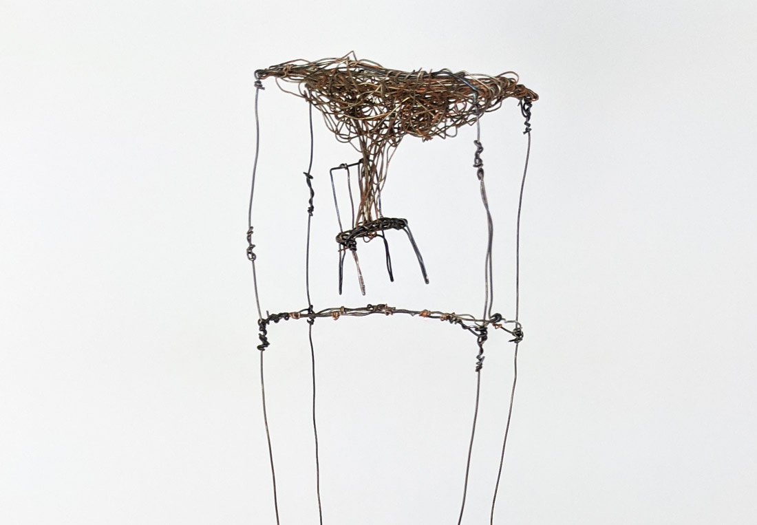Wire sculpture of chair in cube with cloud coming from chair