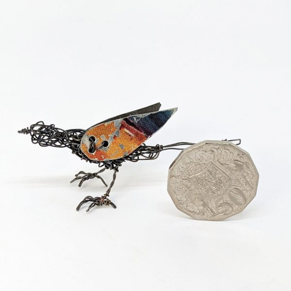 Wire sculpture of bird next to fifty cent coin